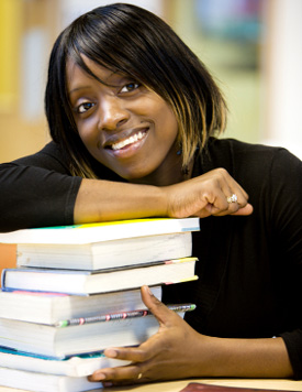student smiling leaning on a stack of books.
