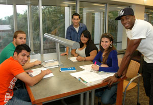 six students in library at a study table