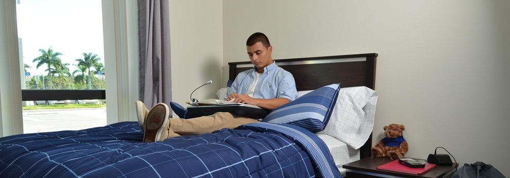 Resident male student studying while in his bedroom in the LightHouse Commons.
